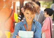 Smiling student carrying folder