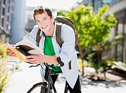 Student reading book on bicycle