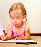 blonde girl drawing with crayons in school