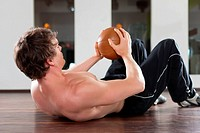 Young man is exercising with medicine ball in gym to strengthen his muscles