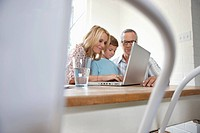 Family using laptop at dining room table
