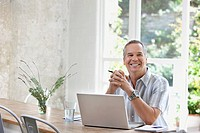 Man using laptop at dining room table