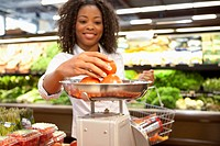 Woman weighing produce in supermarket