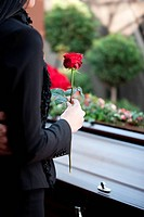 Morning woman on funeral with red rose standing at casket or coffin