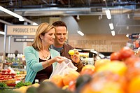 Couple examining produce in supermarket