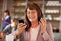 Older woman using cell phone in cafe