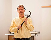 Senior male in a home workshop facing the camera and holding a crowbar