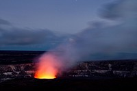 Magma in the Halema´uma´u Crater in the Kilauea Caldera illuminating the rising sulfur dioxide plume against the evening sky, Hawai´i Volcanoes Nation...