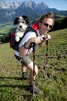 Rambler carrying his dog, that is too small to walk long distances, in his backpack, during ascent to Mt Buchensteinwand, St. Jakob, Tyrol, Austria, E...