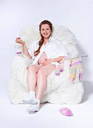portrait of young beautiful pregnant woman in white furry arm_chair knitting baby´s looses