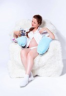 portrait of young beautiful pregnant woman in white furry arm_chair with two soft toy hares