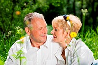 Mature couple sitting out in the green on a beautiful summer day