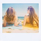 Polaroid of two friends sunbathing on the beach
