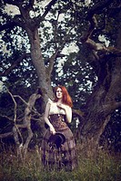Young woman with red hair standing in nature wearing a corset