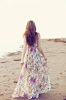 Young woman in long summer dress walking away on beach