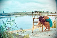 Full body portrait of a young woman resting her head on a golden chair, with a lake in the background and the horizon looking like she is in a bubble