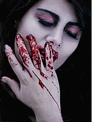 Close_up portrait of a woman with her eyes closed touching her face with her hand with blood dripping through her fingers