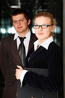 Confident businessman and businesswoman with folder
