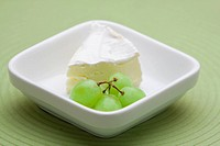 Bowl of white creamy camembert cheese with a bunch of green grapes