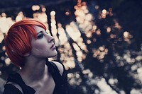 Profile portrait of a young girl with short orange hair and dark make up, looking away, blowing smoke, with blurry lake background