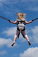 Girl jumping on a trampoline with a safety harness, back side, North Rhine_Westphalia, Germany, Europe