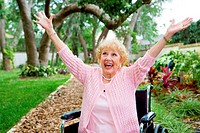 Senior lady in wheelchair is ecstatic as she celebrates freedom from pain.