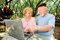 Senior couple on their laptop computer in a beautiful, natural setting.