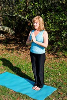Beautiful sixty year old woman doing yoga position in natural outdoor setting.
