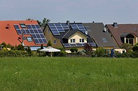 Modern housing estate, multi-family houses with solar panels on the roof, in the countryside