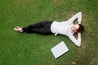 Businesswoman lying on the field with laptop beside her