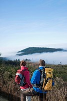 Couple on a hiking trip, enjoying the view onto a misty valley, Black Forest, Baden-Wuerttemberg, Germany, Europe