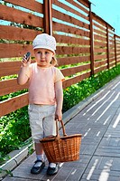 Little child standing with basket in summer time