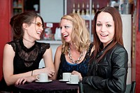 Three young friends joking and laughing in a bistro