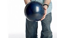 man holds a dark blue marbled bowling ball isolated on white