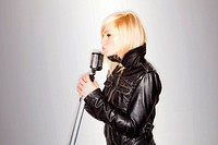 blonde woman holding a retro microphone wearing black jacket , singing rockstar