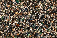 Closeup on wet gravel along the seashore. Small peaces of smooth colored glass are visible too.