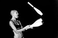 Bald_headed girl juggles on black background.