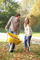 Young couple raking autumn leaves in garden