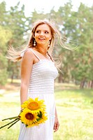 Beautiful young woman in white dress with sunflowers