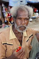 Papuan man offering pepperoni at a vegetable market near Kota Bia, Biak Island off the island of Papua New Guinea, Indonesia, Southeast Asia, Asia