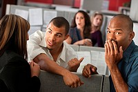 Embarrassed man with hand over mouth standing with coworkers