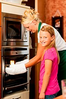 Mother and daughter cooking – they are putting roast in the oven