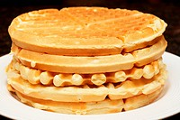 Stack of belgian waffles on white plate