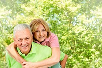 Portrait of happy senior man giving piggyback ride mature woman.