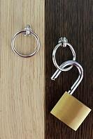 Opened padlock on wooden door