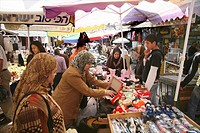 Women examine shoes at a market in the old city section of Jerusalem