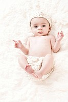 Cute 3_Months Baby wearing a white knit hat and diaper cover