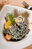fresh seafood black squid ink coulored spaghetti pasta tipycal italian food