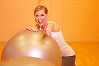 Happy woman in fitness center holding her thumbs up