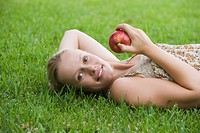Young woman lying on grass holding apple